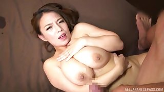 Busty Japanese MILF Oda Mako strokes a cock in between her tits